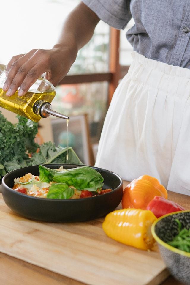 Une femme versant de l'huile sur les légumes.