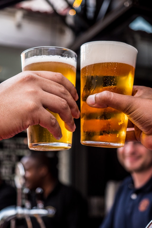 Deux personnes tenant des verres remplis de bière.